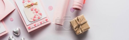 Photo pour Top view of valentines decoration, gifts, hearts and wrapping paper on white background, panoramic shot - image libre de droit