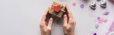 Photo pour Cropped view of woman holding valentines gift box with heart near decoration on white background, panoramic shot - image libre de droit