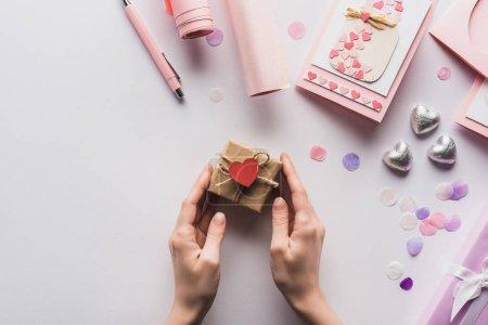 Photo pour Crochet vue d'une femme tenant une valentine boîte-cadeau avec cœur près de la décoration rose sur fond blanc - image libre de droit