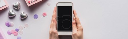 Photo for Partial view of woman holding smartphone near valentines gifts and decoration on white background, panoramic shot - Royalty Free Image