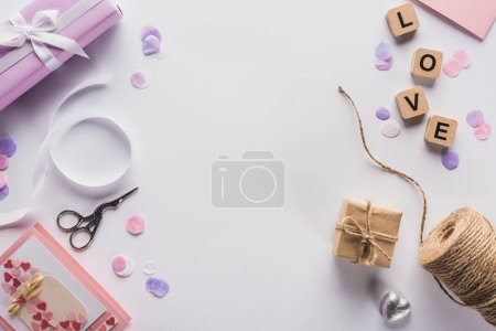 Photo pour Top view of valentines decoration, gifts, handiwork supplies and love lettering on cubes on white background - image libre de droit