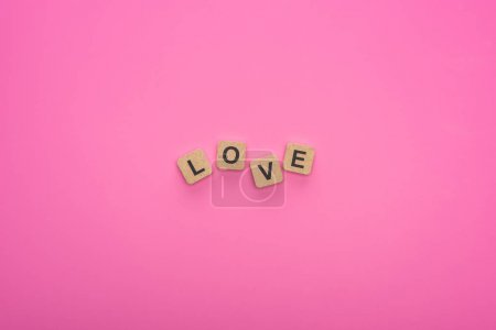 Photo pour Top view of love lettering on wooden cubes on pink background - image libre de droit