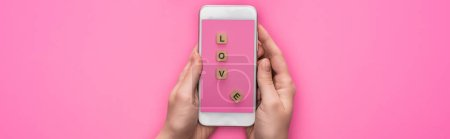 Photo for Partial view of woman holding smartphone with image of cubes with love lettering on pink background, panoramic shot - Royalty Free Image