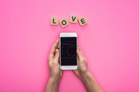 partial view of woman holding smartphone near cubes with love lettering on pink background