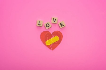 Photo for Top view of love lettering on wooden cubes near broken heart with patch on pink background - Royalty Free Image