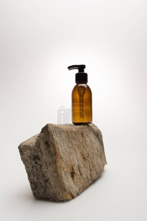 Photo for Dispenser cosmetic bottle on stone on white background with back light - Royalty Free Image
