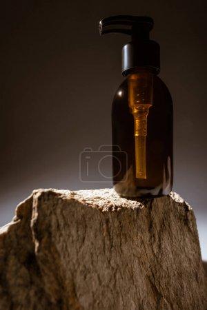 Photo pour Distributeur bouteille cosmétique sur pierre sur fond sombre avec contre-jour - image libre de droit