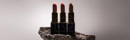 Photo pour Rouge à lèvres sur pierre de couleur foncée sur fond blanc avec fond rétrolumineux, photo panoramique - image libre de droit