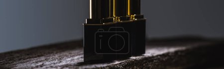 Photo for Lipsticks arranged in line on stone in dark, panoramic shot - Royalty Free Image