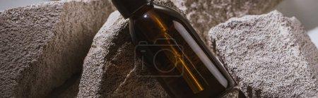 dispenser cosmetic bottle on rocks, panoramic shot