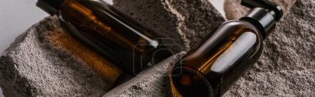 Photo for Dispenser cosmetic bottles on rocks isolated on grey, panoramic shot - Royalty Free Image