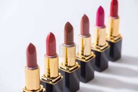 selective focus of assorted lipsticks in luxury tubes in line on white background
