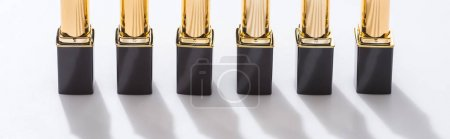 Photo for Lipsticks in luxury tubes in line on white background, panoramic shot - Royalty Free Image