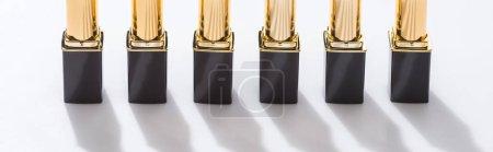 Foto de Lápiz labial en tubos de lujo en línea sobre fondo blanco, plano panorámico - Imagen libre de derechos