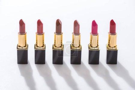 Photo pour Assortiment de rouge à lèvres en tubes de luxe en ligne sur fond blanc - image libre de droit