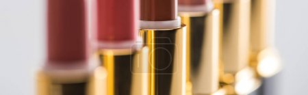 Photo for Close up view of assorted lipsticks in luxury tubes in line isolated on white background, panoramic shot - Royalty Free Image