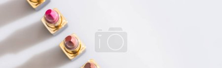 Photo pour Vue de dessus des rouges à lèvres assortis dans des tubes de luxe en ligne sur fond blanc, vue panoramique - image libre de droit