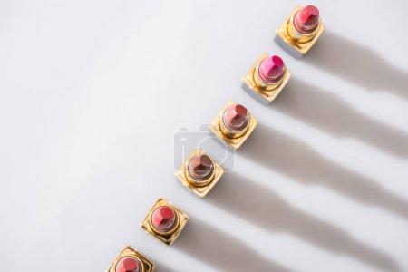 Photo pour Top view de divers rouges à lèvres dans des tubes de luxe en ligne sur fond blanc - image libre de droit