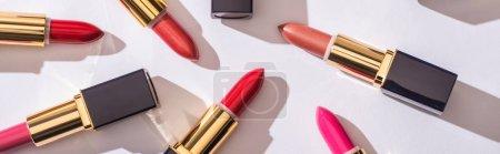 Photo pour Vue de dessus des rouges à lèvres assortis dans des tubes de luxe sur fond blanc, vue panoramique - image libre de droit