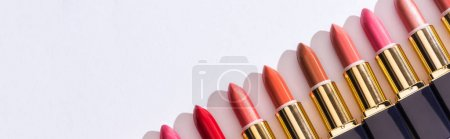 Photo for Top view of assorted lipsticks in luxury tubes in line on white background, panoramic shot - Royalty Free Image