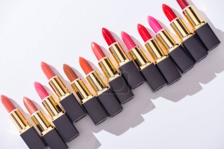 Photo pour Top view of assorted lipsticks in luxury tubes on white background - image libre de droit