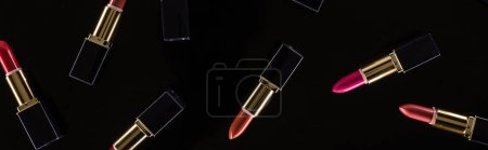 Photo for Top view of assorted lipsticks in luxury tubes isolated on black, panoramic shot - Royalty Free Image