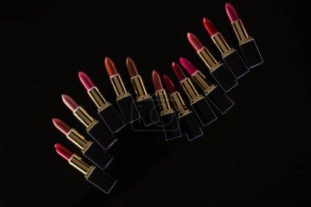 Photo pour Top vue d'un assortiment de rouge à lèvres dans des tubes de luxe isolés sur noir - image libre de droit