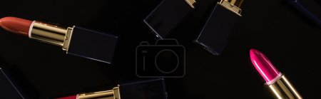 Photo for Top view of assorted lipsticks in luxury tubes scattered isolated on black, panoramic shot - Royalty Free Image