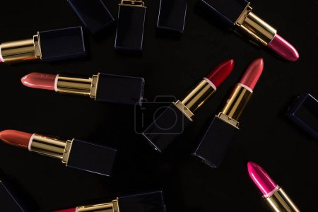 Photo pour Top view of assorted lipsticks in luxury tubes scattered isolated on black - image libre de droit