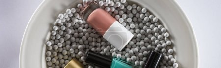 Photo for Top view of assorted nail polish in bottles on plate with grey decorative beads, panoramic shot - Royalty Free Image