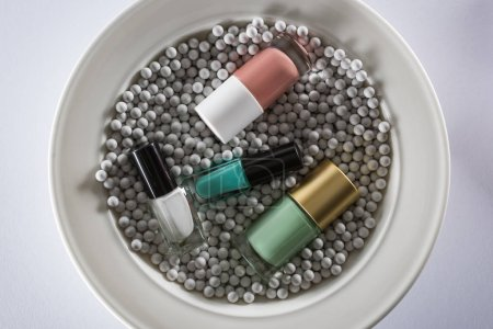 Photo for Top view of assorted nail polish in bottles on plate with grey decorative beads - Royalty Free Image