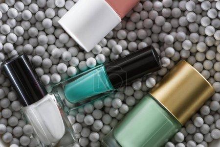 Photo pour Top vue d'un assortiment de vernis à ongles dans des bouteilles en perles décoratives grises - image libre de droit