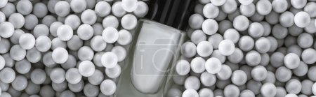 Photo pour Top view of white nail polish in bottle among grey decorative beads, panoramic shot - image libre de droit