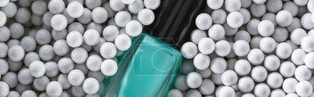 Photo pour Top view of blue nail polish in bottle among grey decorative beads, panoramic shot - image libre de droit
