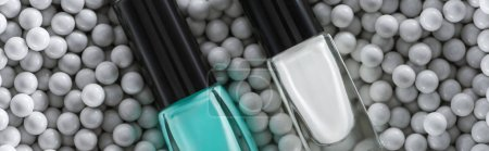 Photo for Top view of blue and white nail polish in bottles in grey decorative beads, panoramic shot - Royalty Free Image