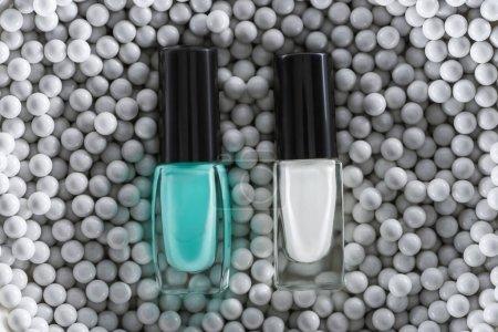 Photo pour Top vue du vernis à ongles bleu et blanc dans des bouteilles en perles décoratives grises - image libre de droit