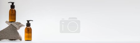 Photo for Dispenser cosmetic bottles with stones on white background with back light, panoramic shot - Royalty Free Image