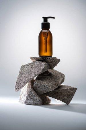 Photo pour Distributeur bouteille cosmétique sur pierres sur fond blanc avec contre-jour - image libre de droit