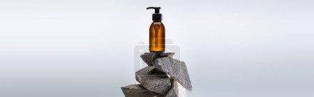Photo pour Distributeur bouteille cosmétique sur pierres sur fond blanc avec rétrolumière, photo panoramique - image libre de droit
