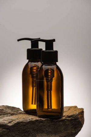 Photo pour Bouteille cosmétique distributeur sur pierre sur fond blanc avec contre-jour - image libre de droit
