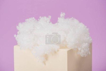 Photo pour Nuage pelucheux blanc en laine de coton sur cube isolé sur fond violet - image libre de droit