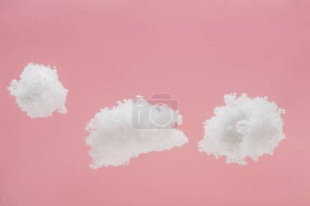Photo pour Nuages blancs duveteux faits de ouate isolés sur rose - image libre de droit