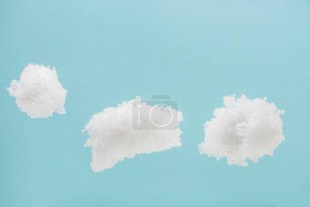Photo pour Nuages pelucheux blancs en laine de coton isolé sur fond bleu - image libre de droit