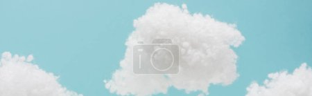 white fluffy clouds made of cotton wool isolated on blue background, panoramic shot