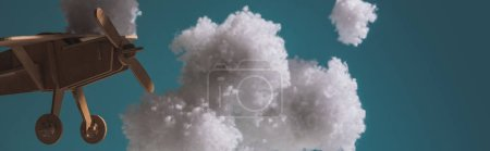 Photo for Wooden toy plane flying among white fluffy clouds made of cotton wool in dark, panoramic shot - Royalty Free Image