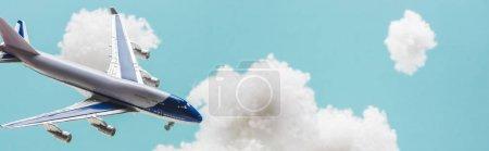 Photo pour Avion jouet volant parmi les nuages pelucheux blancs en laine de coton isolé sur bleu, plan panoramique - image libre de droit