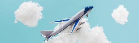 Foto de Avión de juguete que vuela entre nubes de lana de algodón blanquecinas hechas de lana aislada en azul, tiro panorámico. - Imagen libre de derechos