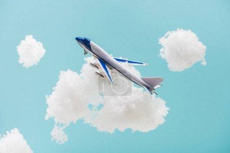 Photo pour Jouet avion volant parmi les nuages duveteux blancs en laine de coton isolé sur bleu - image libre de droit