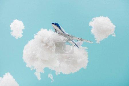 Foto de Avión de juguete que vuela entre nubes de humo blancas hechas de lana de algodón aislada en azul. - Imagen libre de derechos