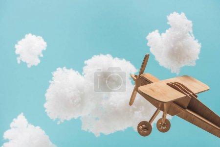 Photo pour Avion jouet en bois volant au milieu de nuages blancs moelleux faits de ouate isolé sur bleu - image libre de droit